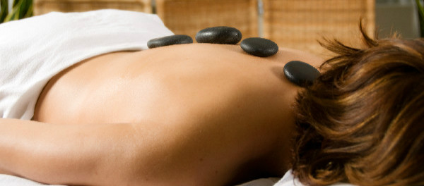 woman in a day spa with hot stones on her back