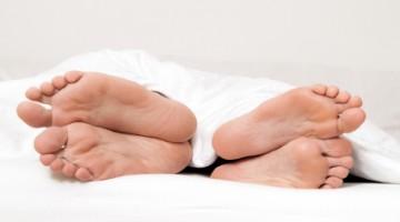 Dier Füße eines Paares im Bett. Trennung und Scheidung