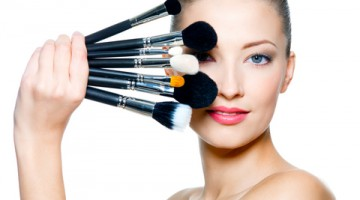 Portrait of the beautiful woman with make-up brushes near attractive face. Adult girll posing over white background